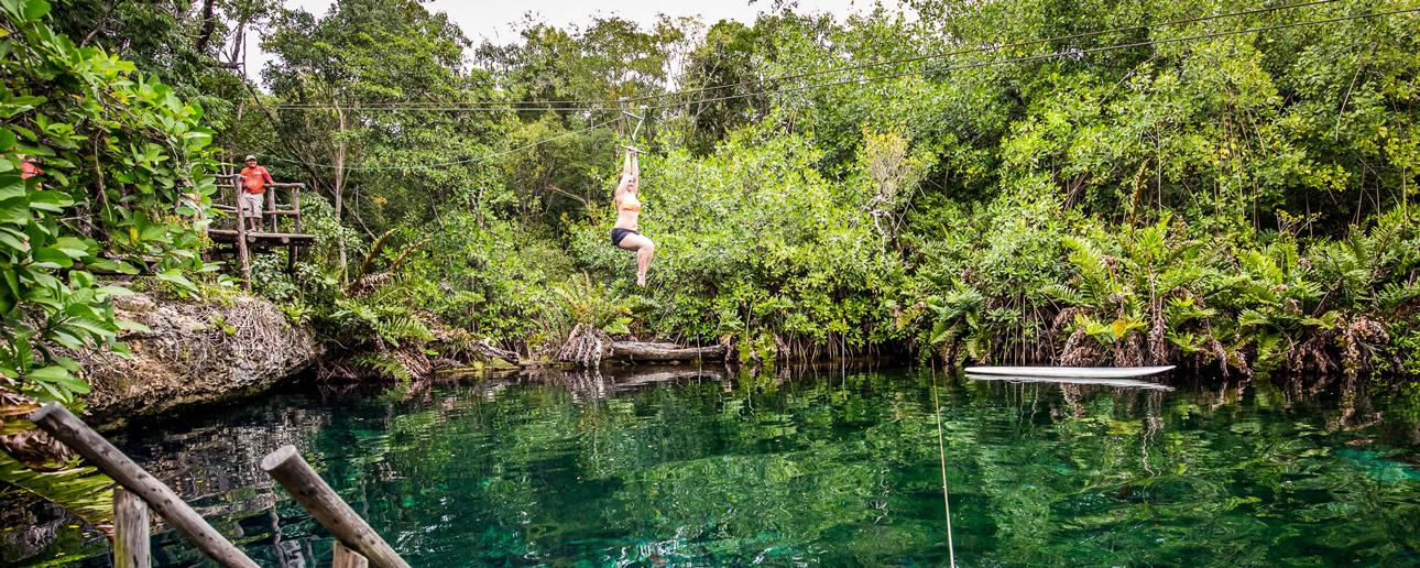 Man ziplining over water in the jungle